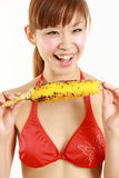 Young Japanese woman wearing bikini with grilled corn Stock Photography