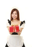 Young Japanese woman wearing french maid costume offering a gift Stock Photography