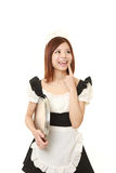 Young Japanese woman wearing french maid costume thinks about something. Studio shot of young Japanese woman on white background Stock Images