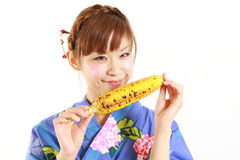 Young Japanese woman wearing kimono with grilled c Royalty Free Stock Photography