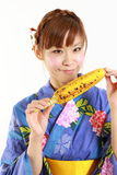 Young Japanese woman wearing kimono with grilled c Stock Photography