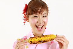 Young Japanese woman wearing kimono with grilled c Royalty Free Stock Image