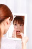 Young Japanese woman worries about dry rough skin Royalty Free Stock Image