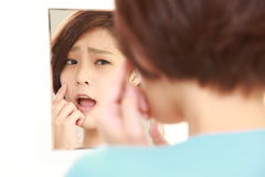 Young Japanese woman worries about dry rough skin Stock Images