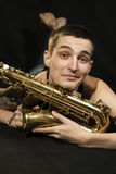 Young jazzman lie on the floor with saxophone Stock Photos