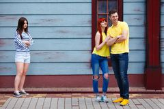 Young jealous girl looking at dating couple royalty free stock image
