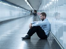 Young businessman crying abandoned lost in depression sitting on ground subway royalty free stock photos