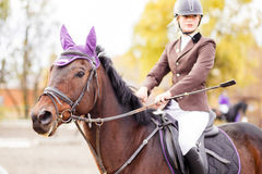Young jockey girl riding horse on competition Stock Image