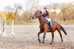 Young jockey girl riding horse on competition Royalty Free Stock Photo