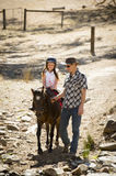 Young jockey kid riding pony outdoors happy with father role as horse instructor in cowboy look Royalty Free Stock Images