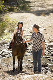 Young jockey kid riding pony outdoors happy with father role as horse instructor in cowboy look Stock Images