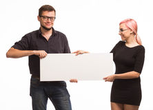 Young jocular couple showing presentation pointing placard Stock Image