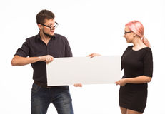 Young jocular couple showing presentation pointing placard Stock Images