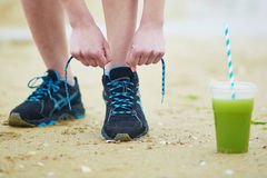 Young jogger with green vegetable smoothie. Tying sport running shoes laces. Fitness and healthy lifestyle concept Royalty Free Stock Photography