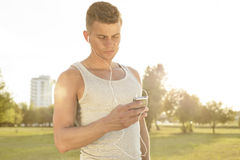 Young jogger listening to music through cell phone in park Stock Image
