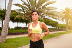 Young jogger listening to music while running. Young jogger in sport tank top listening to music while running in summertime Stock Images