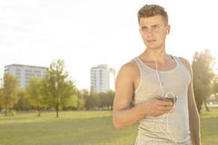 Young jogger looking away while listening music through cell phone in park Stock Photo