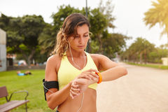 Young jogger looking at smart bracelet outdoors Royalty Free Stock Photo