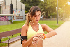 Young jogger looking at smart watch while standing Royalty Free Stock Image