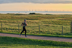 Young jogger in old environment. Malmo, Sweden – August 20, 2013: Young woman jogging along the meadows in Bunkelfostrand at Oresund waterfront south of Malmo Royalty Free Stock Photos