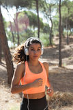 Young jogger running towards viewer with white headphones Royalty Free Stock Image