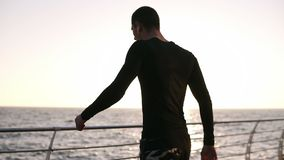 Young jogger stopped to have a little rest before long distance running. He wears a sports black shirt with white. Earphones. Early morning in front the sea stock footage