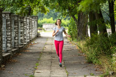 Young jogging woman running through the summer park road. Stock Image