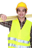 Young joiner carrying planks royalty free stock image