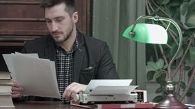 Young journalist reading printed articles sitting at the desk with typewriter stock footage