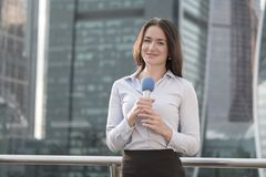 Journalist is reporting on a business center background. Young journalist is reporting on a business center background Royalty Free Stock Photography