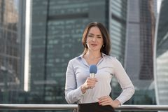 Journalist is reporting on a business center background. Young journalist is reporting on a business center background Stock Photography