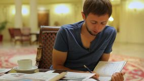 Young journalist taking notes, preparing for press conference at hotel lobby stock footage