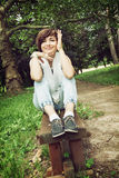 Young joyful brunette sitting on the park bench Stock Images