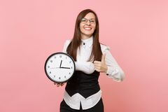 Young joyful business woman in suit and glasses holding alarm clock and showing thumb up on pastel pink royalty free stock photo