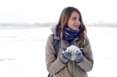 A young and joyful Caucasian girl in a brown coat holds a snowball in the background of a horizon line stock image