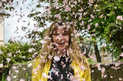 Young joyful, charming girl in the sakura-colored petals falling in the wind royalty free stock image