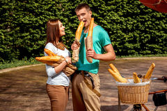 Young and joyful couple eating a lot of baguettes in the park Stock Image