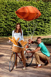 Young and joyful couple having fun in the park with bicycle and Stock Image