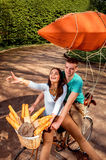 Young and joyful couple having fun in the park with bicycle and Royalty Free Stock Photos