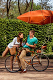 Young and joyful couple having fun in the park with bicycle and. Airship on it Royalty Free Stock Images