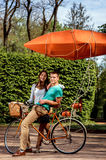 Young and joyful couple having fun in the park with bicycle and Stock Images