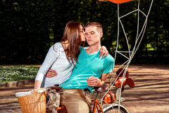 Young and joyful couple having fun in the park with bicycle and Royalty Free Stock Photo