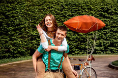 Young and joyful couple having picky back ride in the park with Royalty Free Stock Photography