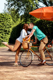 Young and joyful couple hugging in the park with bicycle and air. Ship on it Stock Photo