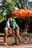 Young and joyful couple hugging in the park with bicycle and air. Ship on it Royalty Free Stock Photography