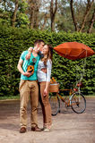 Young and joyful couple kissing and standing with old photo came Royalty Free Stock Photo