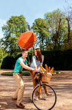 Young and joyful couple learning to ride a bicycle and airship o Stock Images