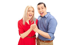 Young joyful couple singing on microphone Stock Images