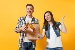 Young joyful couple woman man sport fan cheer up support team clinking beer bottles hold italian pizza in cardboard. Young joyful couple women men sport fan royalty free stock photography