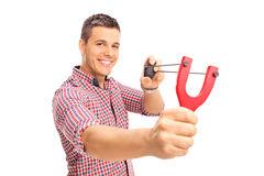 Young joyful guy shooting a rock from a slingshot Royalty Free Stock Photography